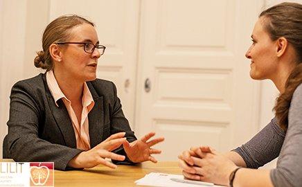 Zwei Frauen sitzen an einem Tisch. Es geht um effektives Konfliktmanagement.