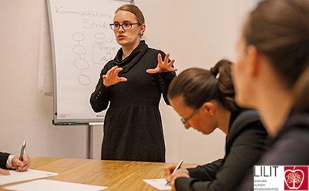 Eine Frau steht vor einem Flipchart und erklärt etwas. Am Tisch vor ihr sitzen zwei junge Frauen, hören zu und schreiben mit.