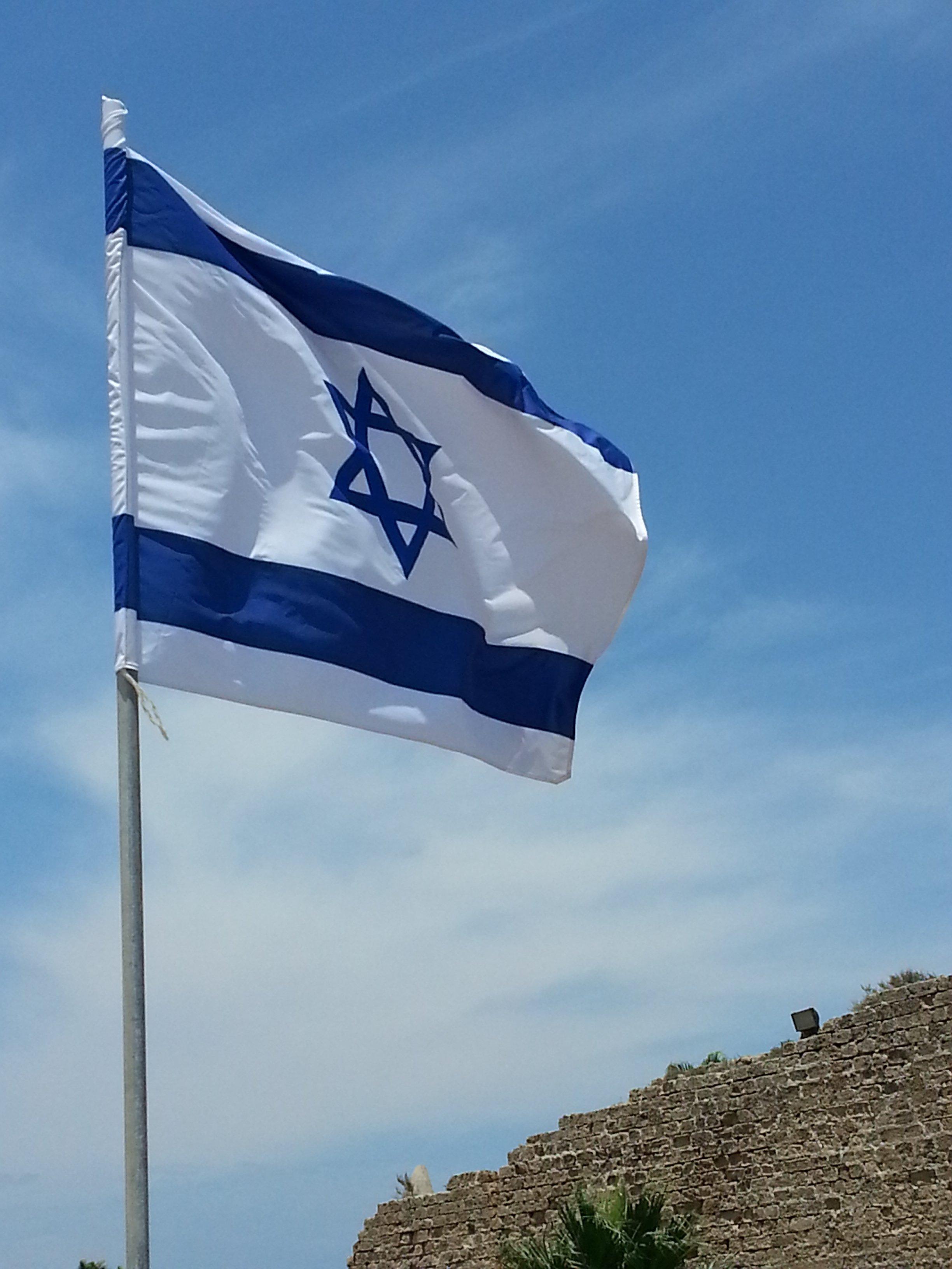 Israel-Training: Eine israelische Flagge mit dem Davidsstern weht über Massada. Ein gewohnter Anblick beim Arbeiten in Israel.