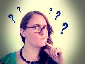Eine Frau, die fragend schaut. Neben ihrem Kopf Fragezeichen. Wie antwortet man nur auf fiese Fragen?
