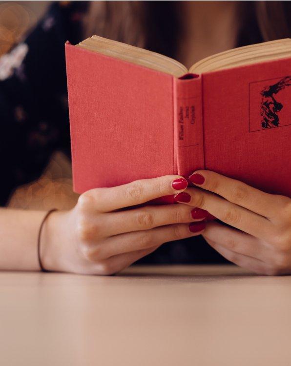 Ein rotes Buch in der Hand - so könnte der erste Schritt zum Perspektivwechsel durch Lesen aussehen.
